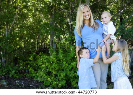 A beautiful pregnant mother with her cute blond children touching her growing tummy. Lots of copy space