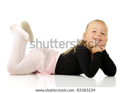 A beautiful preschool ballerina laying on her belly.  Isolated on white. - stock photo