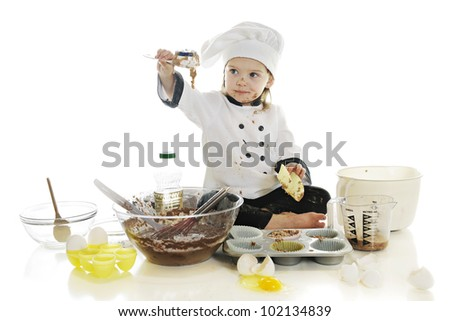 "A beautiful preschool ""chef"" playing in the batter of her first cake.  On a white background. - stock photo"