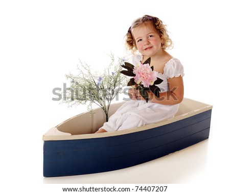A beautiful preschool girl sitting in a small blue boat with spring flowers.  Isolated on white.