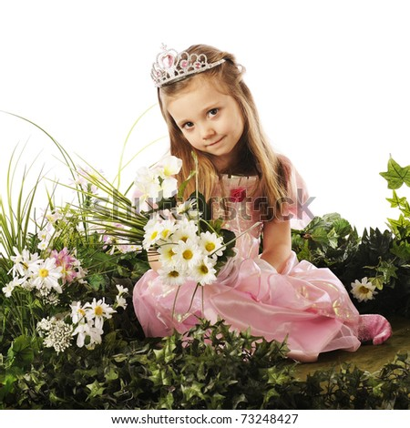 A beautiful preschool princess sitting among flowers and foliage while holding a bouquet. - stock photo