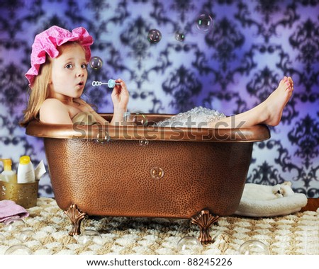 A beautiful preschooler blowing bubbles while wearing a bath bonnet in an old-time copper tub. - stock photo