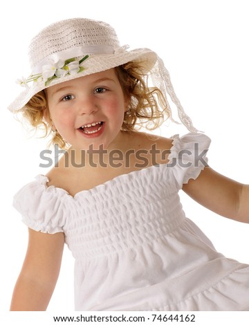 A beautiful preschooler delighted with her white Easter bonnet and dress. - stock photo