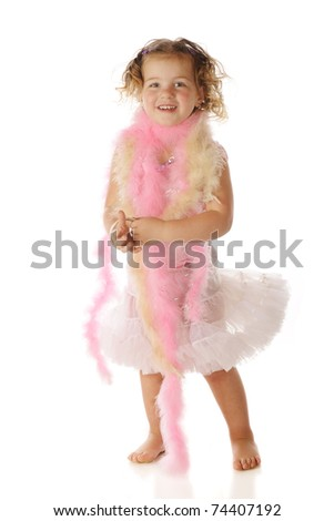 A beautiful preschooler dressed in a petticoat and boas, happily swishing the skirt by shaking her behind.  Isolated on white. - stock photo