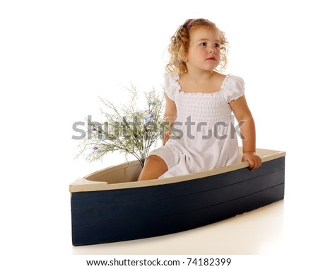 A beautiful preschooler in a small blue boat with a bouquet of blue wild flowers.  Isolated on white. - stock photo