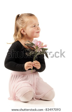 A beautiful preschooler kneeling with a pink flower while in her ballerina outfit. - stock photo