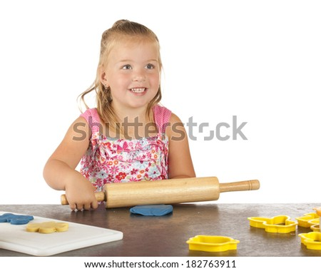 A beautiful preschooler rolling kiddie dough to cut out with cookie cutters. - stock photo