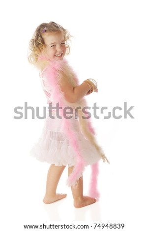 """A beautiful preschooler wrapped in boas, happily looking over her shoulder as she swishes her petticoat by shaking her """"boodie.""""  Isolated on white. - stock photo"""