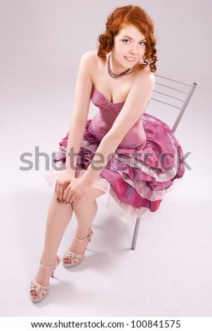 A beautiful red-haired girl sitting on a chair - stock photo