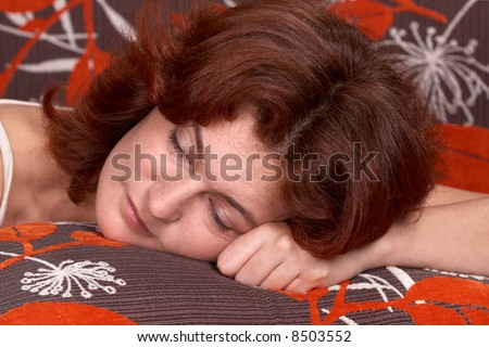A beautiful red-haired woman taking a nap on her bed.