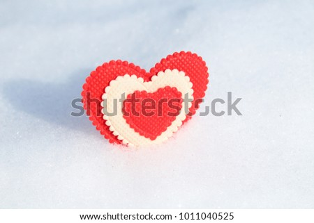 A beautiful red soft heart made of cloth in the snow. Close-up. Isolated.