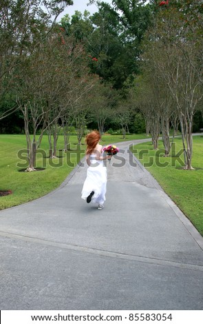 A beautiful redheaded bride running away, or rushing late - stock photo