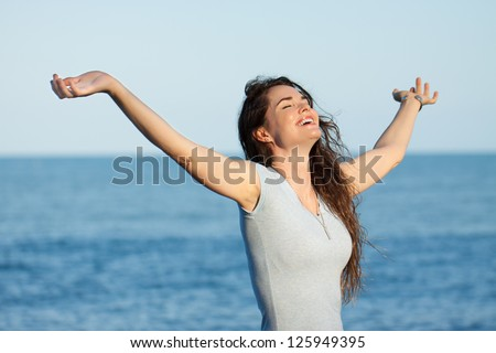 A beautiful relaxed woman with arms stretched out standing on a beach. - stock photo