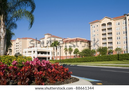 A beautiful resort surrounded by palm trees and flowers with blue sky background - stock photo