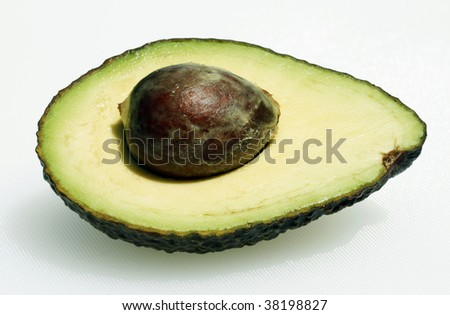 A beautiful ripe avocado sliced in two showing the big brown round seed and the succulent flesh.