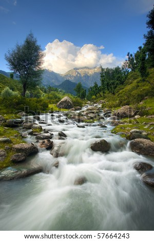 A beautiful river and Himalayan mountain background in Kashmir's Aru Valley in vertical landscape. - stock photo