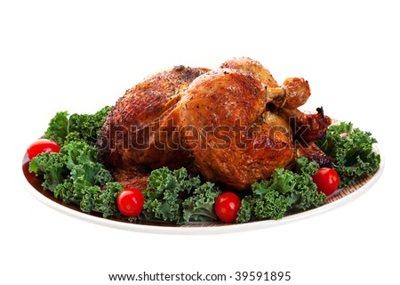 A beautiful roasted chicken on a garnished platter.  Shot on white background.