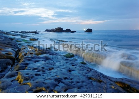 A beautiful rocky beach on a cloudy gloomy morning at Yehliu Coast north to Taipei in Taiwan ~ Fascinating scenery of Yehliu Geopark under dramatic dawning sky - stock photo