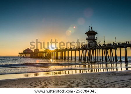 A beautiful romantic sunset on the pier overlooking a the ocean sand at sunset. - stock photo
