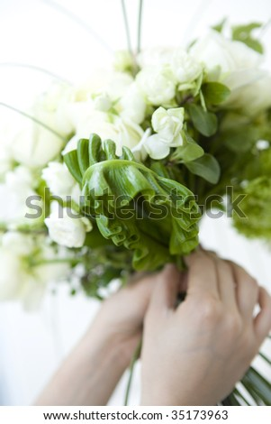 A beautiful rose bouquet and holding hands isolated on white - stock photo