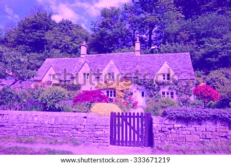 A beautiful row of Cotswold country Cottages and gardens in summer with blue sky and clouds, in the heart of The Cotswolds, Gloucestershire, England, United Kingdom - stock photo