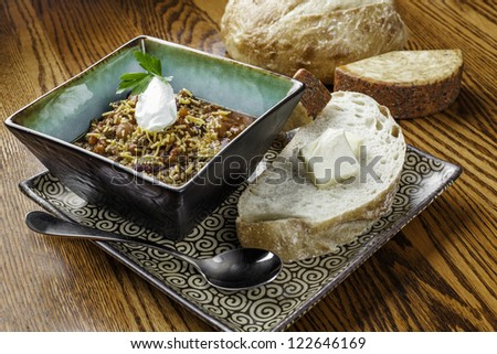 A beautiful rustic bowl of spicy chili with hearty white bread and cheese on a nice wooden table. - stock photo