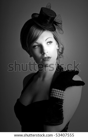 a beautiful 1930s styled woman in a low key black and white setting