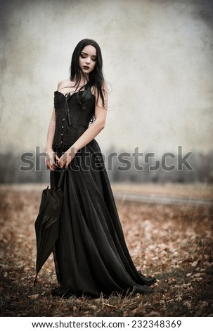 A beautiful sad goth girl holds black umbrella. Grunge texture effect