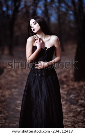 A beautiful sad goth girl stands in a grove - stock photo