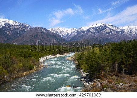 A beautiful scene of Japan Alps and natural stream over blue sky