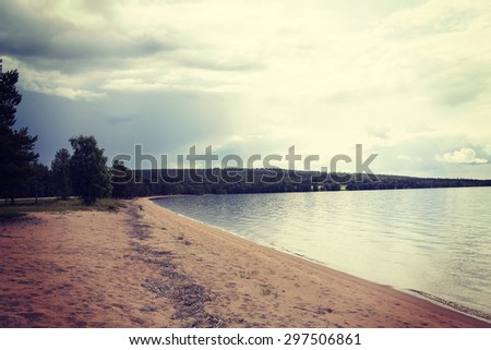 A beautiful scene with crystal clear water in Finland in the summer time. Some clouds are in the sky. Image has a vintage effect applied. - stock photo