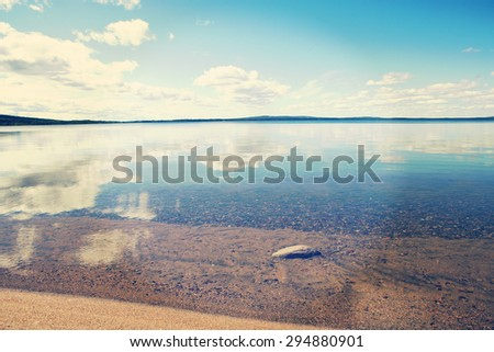 A beautiful scene with crystal clear water in Finland in the summer time. Some clouds in the sky giving a deep contrast to the image and a rock is visible through water. Image has a vintage effect. - stock photo