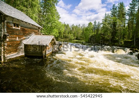 A beautiful scenery with a river rapids and an old mill building in Finland