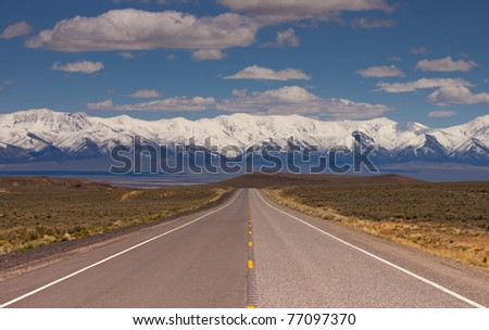 A beautiful scenic of a road, mountains and clouds.