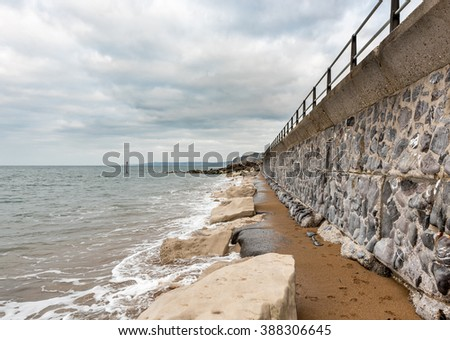 A beautiful seawall disappearing into the distance along the coastal path in southern England - stock photo
