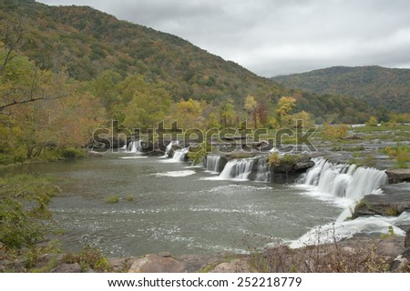 A beautiful set of waterfalls surrounded by the colors of fall foliage - stock photo