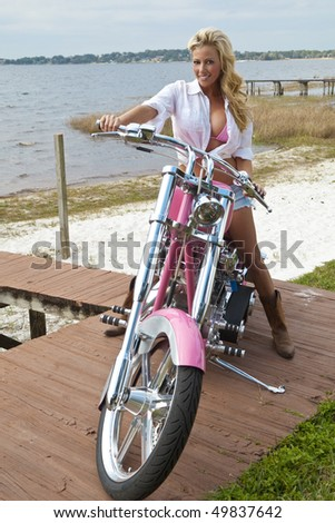 A beautiful sexy blond woman wearing a pink bikini and denim jeans shorts sitting on a pink chopper motorbike next to a beach and a lake