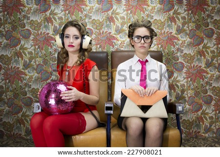 a beautiful sexy disco woman in a train chair filmed twice interacting with herself. One of her characters is serious the other playful  - stock photo