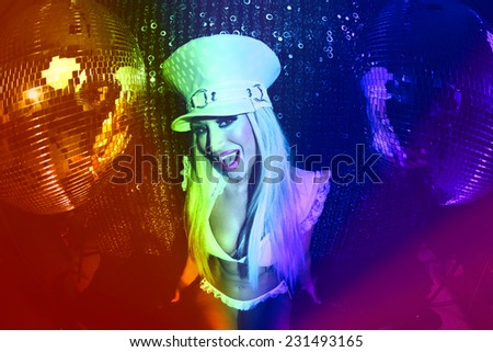 a beautiful sexy female drag artist dancing and posing in character in a disco/club setting
