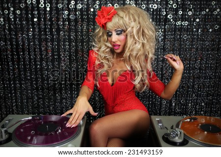 a beautiful sexy female drag artist djing and playing music in character in a disco/club setting  - stock photo