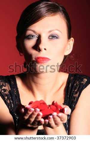 A beautiful sexy women blowing rose petals on red background - stock photo