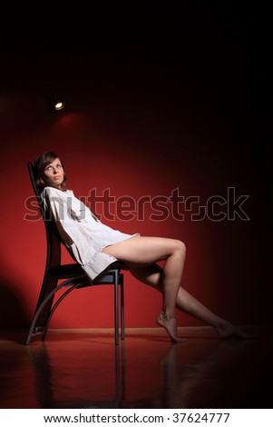 A beautiful sexy women on a chair on  red background - stock photo