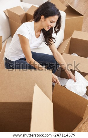 A beautiful single young woman packing or unpacking boxes and moving into a new house or home - stock photo