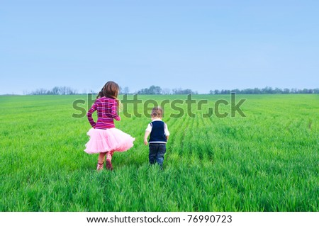 A beautiful sister runing with her cute little brather on the grass - stock photo
