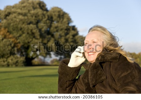A beautiful sixties lady has a friendly chat on her cellphone while sitting in the park - stock photo