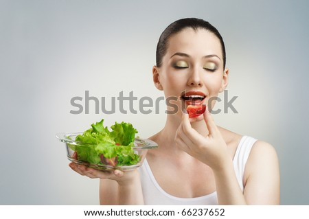 A beautiful slender girl eating healthy food - stock photo