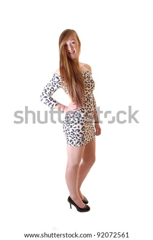 A beautiful slim teenage girl with long brunette hair, standing in a short dress and high heels in the studio for white background. - stock photo