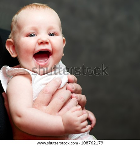 A beautiful smiling baby in the hands of his father - stock photo
