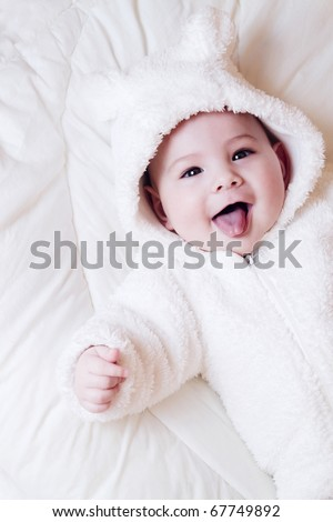 A beautiful smiling baby lying on white background - stock photo