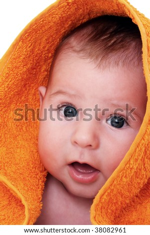 A beautiful smiling baby wrapped in a furry orange blanket